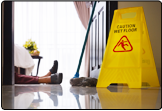 A picture of a woman on the floor with just her legs in show. She has likely fallen because of a slip or trip as there is a mop and a slip hazard sign present