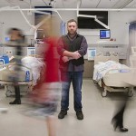 picture of a man stood in a hospital ward with lots of nurses and doctors rushing around him. Long exposure image.