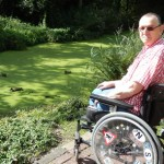 Man sat in a wheelchair in a garden